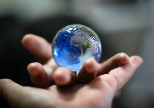 Hands holding a glass ball that looks like Earth