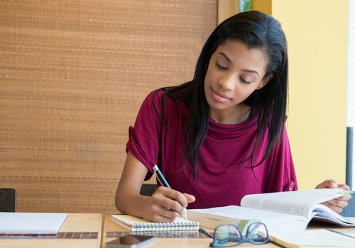 Woman reading a textbook and writing on a notepad