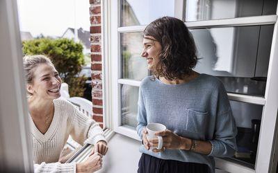 Two happy women talking through the window