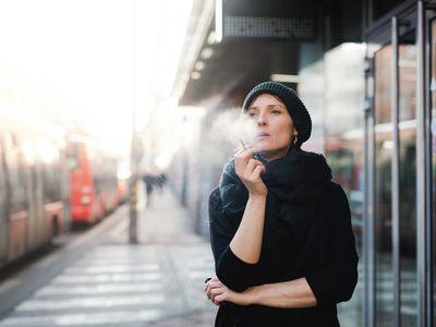 Woman standing outside smoking a cigarette