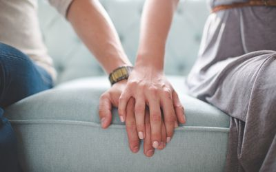 man and woman's hands touching on couch