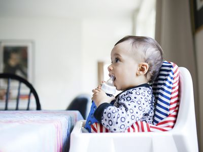 baby girl drinking milk from bottle while sitting on high chair