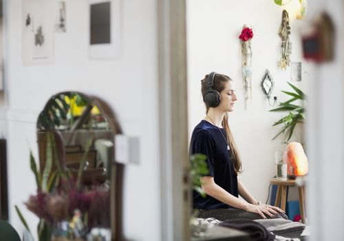 woman meditating in her apartment with headphones on