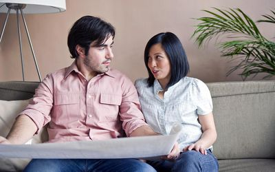 Married couple in disagreement looking at plans.