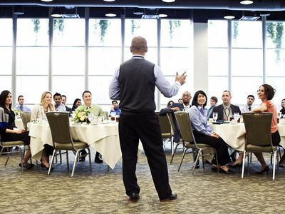 Speaker at business luncheon talking in front of crowd