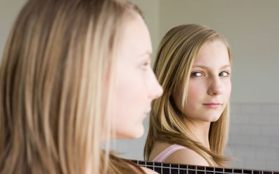 blonde woman looking at herself in a mirror