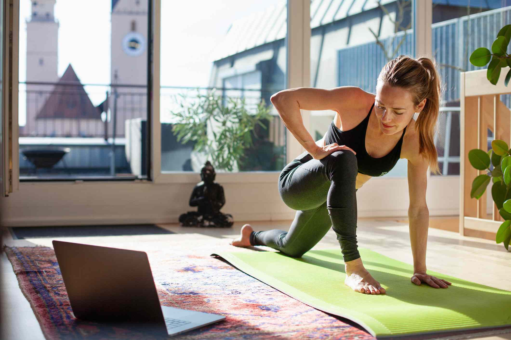 Young woman in athletic clothing doing yoga in her apartment