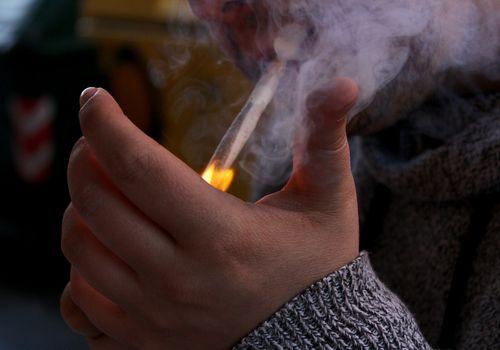 Man Igniting Marijuana Joint With Lighter