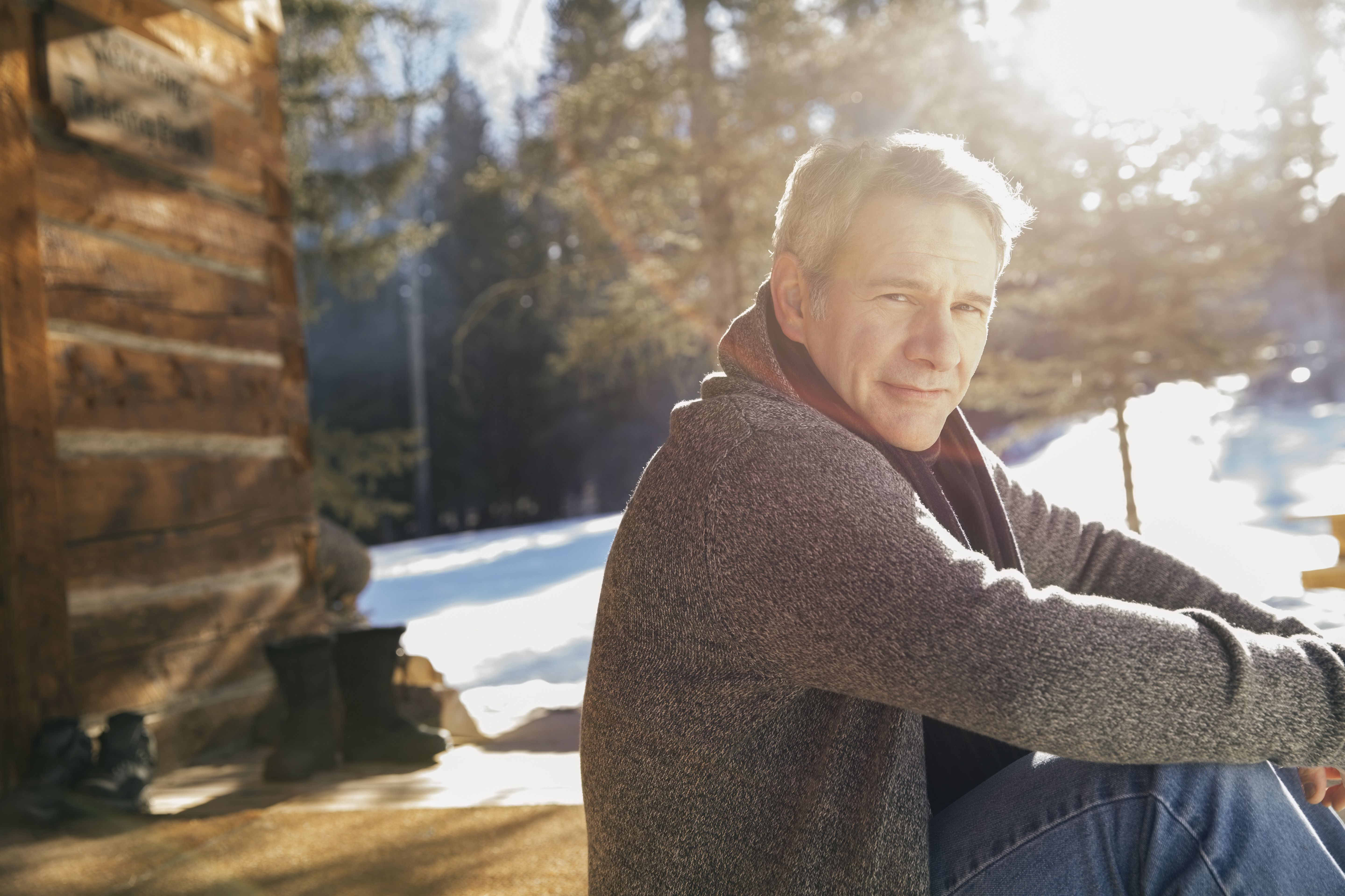 Portrait of confident man relaxing outside log cabin