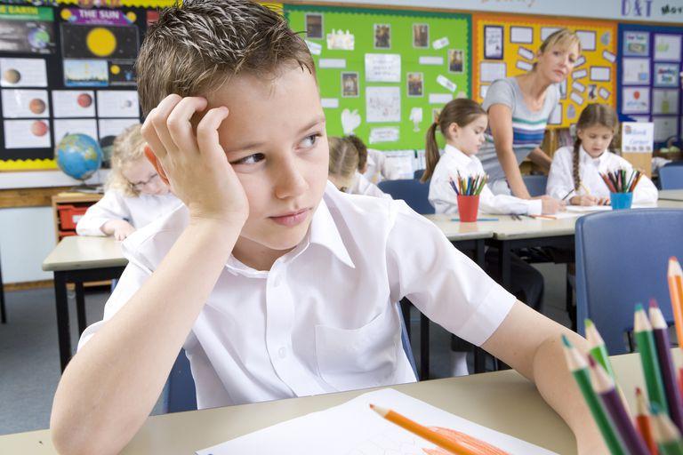 Bored school boy sitting in classroom