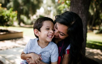 A mom holds her smiling son in a park on a sunny day.