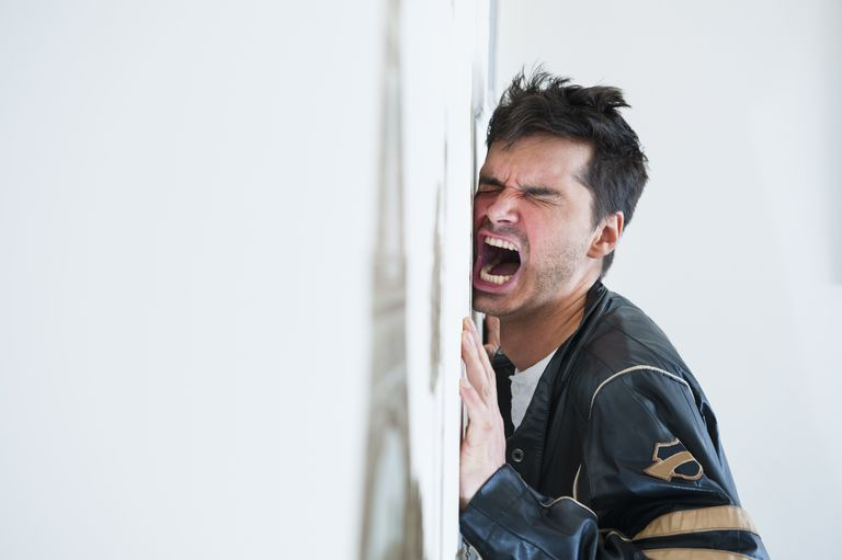 Frustrated mid adult man screaming at the wall