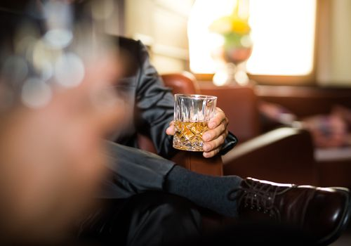 Businessman holding whiskey glass