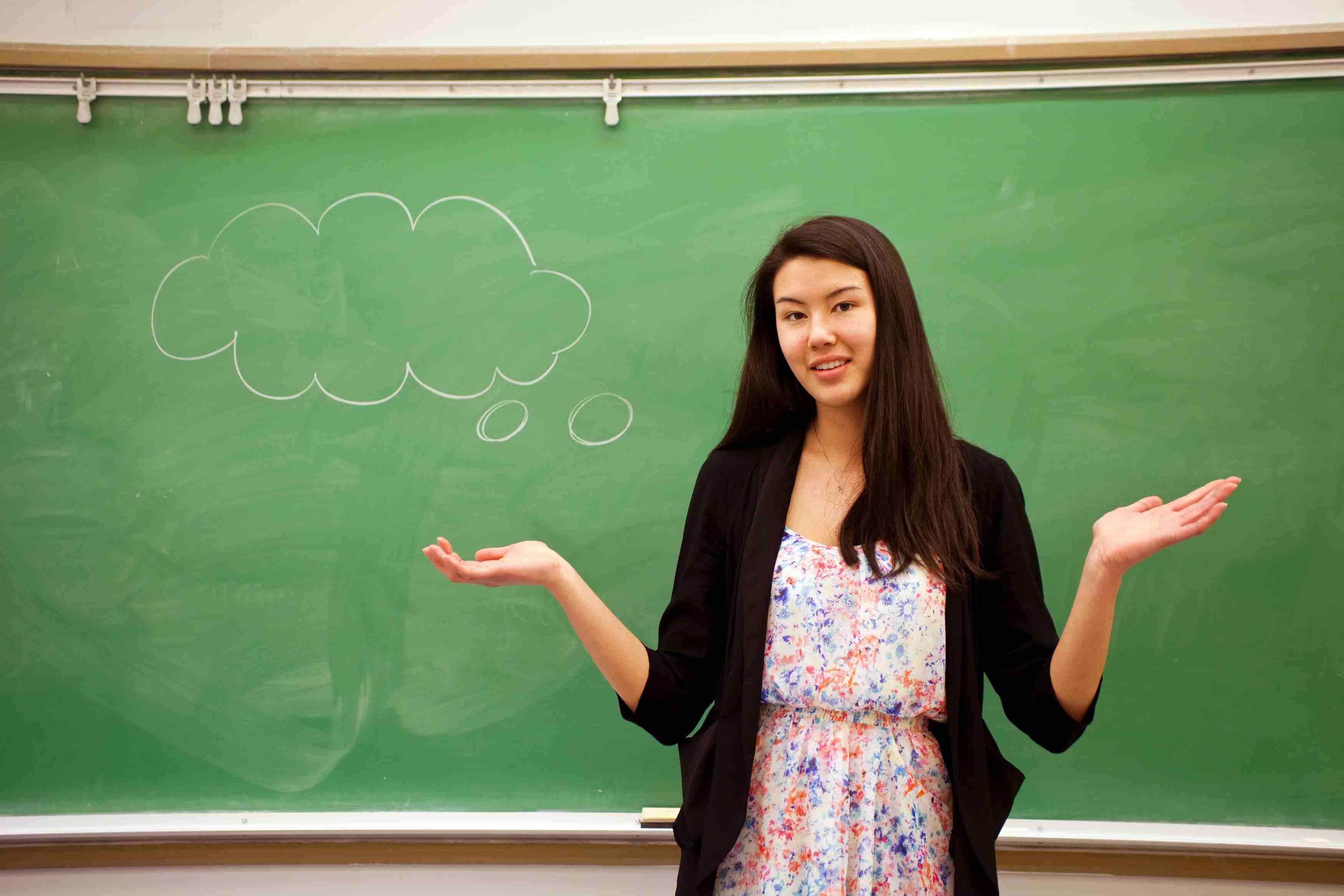 Woman talking in front of chalkboard