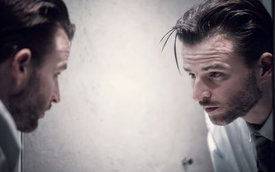 pensive man looking into mirror