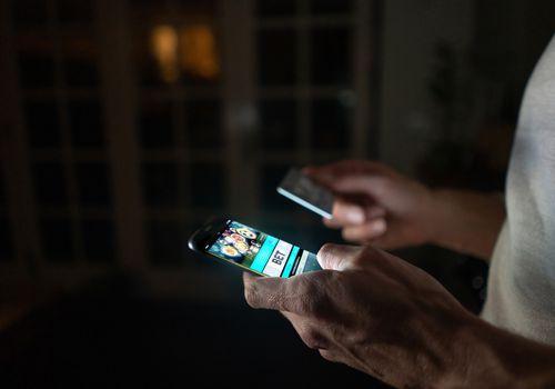 man holding smart phone playing gambling game