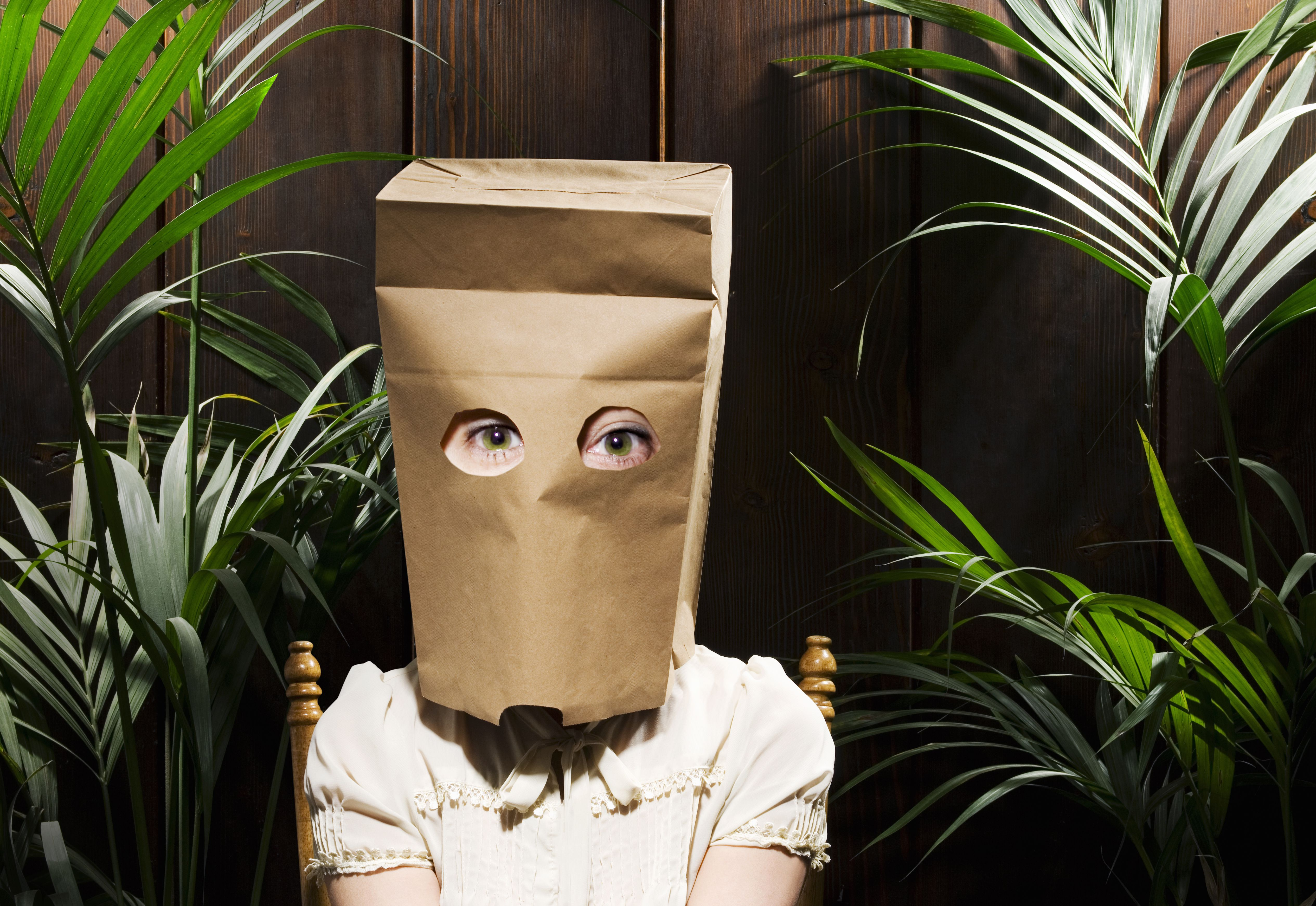 Woman with paper bag over head, eyes cut out