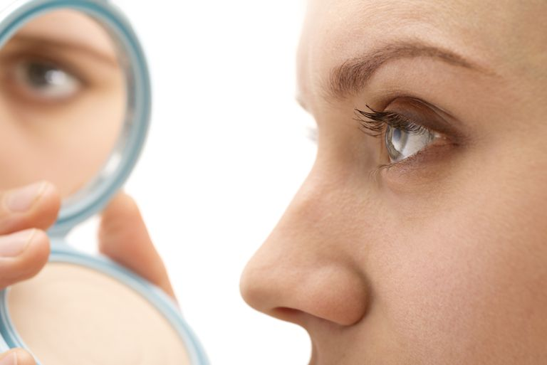 Woman applying makeup eye reflection