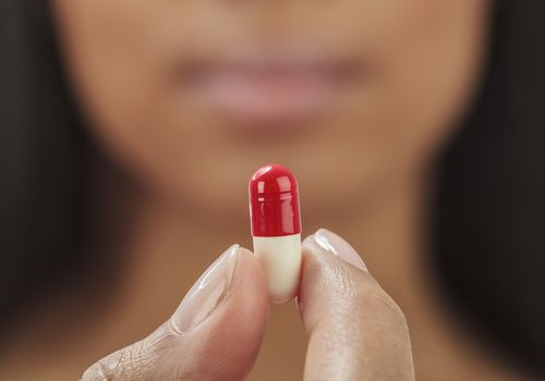 Close up of mixed race woman holding medication capsule