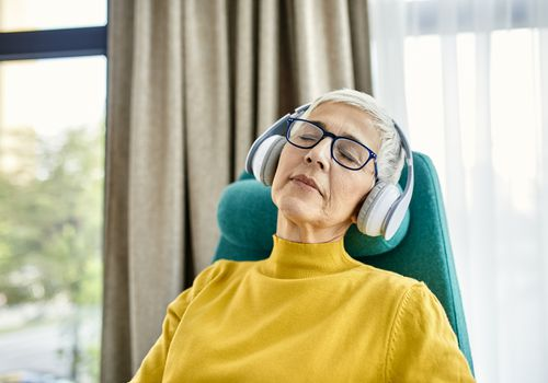 Older woman with headphones on peacefully dozing off to sleep
