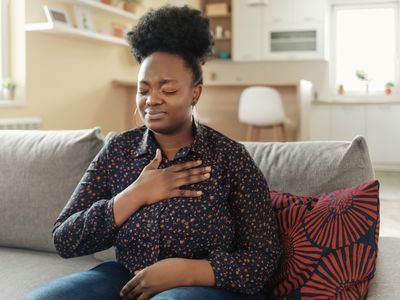 Black woman with eyes closed and hand over chest