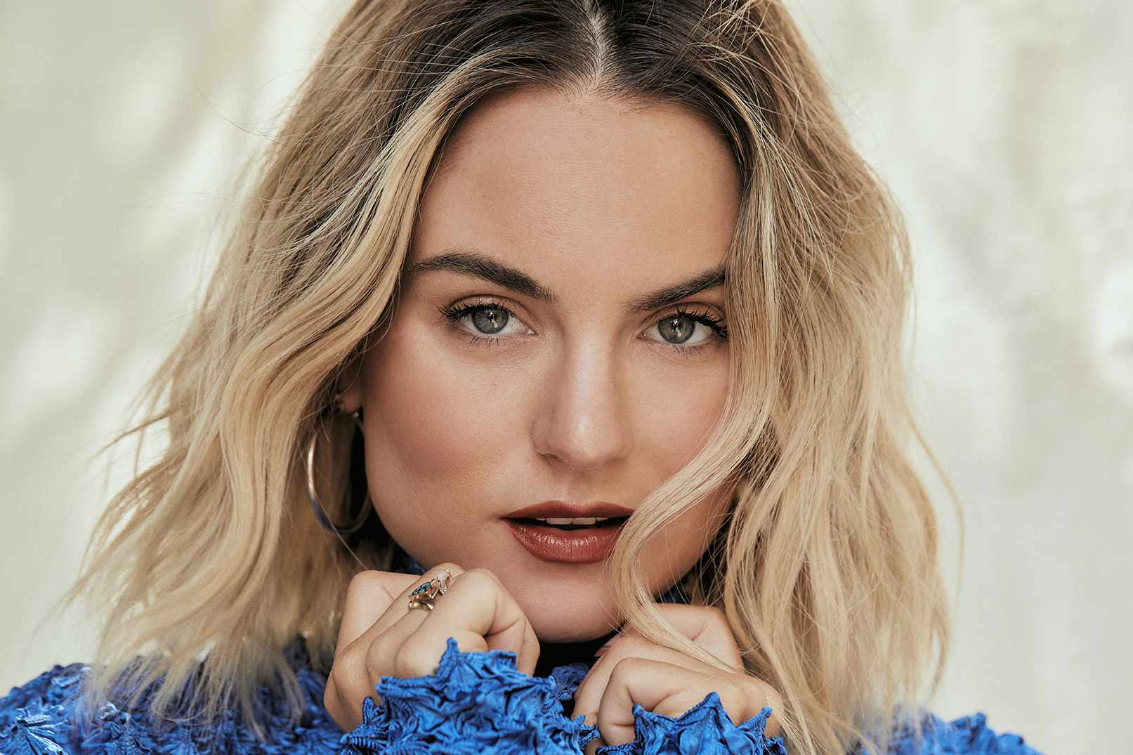 JoJo in blue top, hands clenched under her face