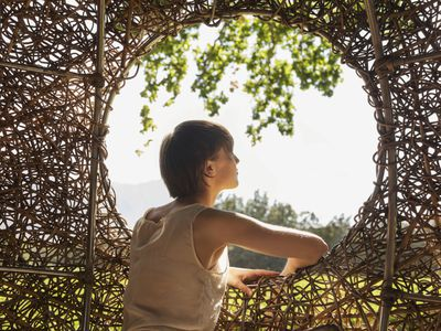Woman looking through opening in an arbor