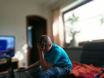 boy sits on his bed on his computer