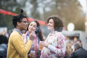 Three friends at a festival smoking and drinking