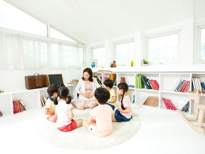 group of young children circled around teacher on the floor