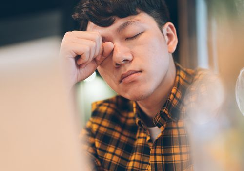 Exhausted young man rubbing eyes in cafe