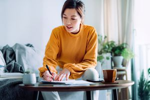 Young Asian woman holding a pen and signing paperwork in the living room at home