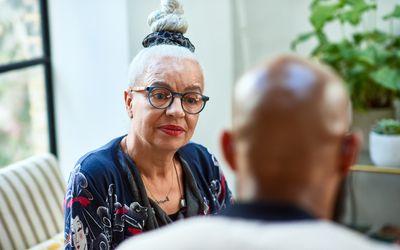 Senior woman with hair bun listening to friend