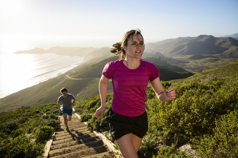 couple jogging up steps on outdoor hillside trail