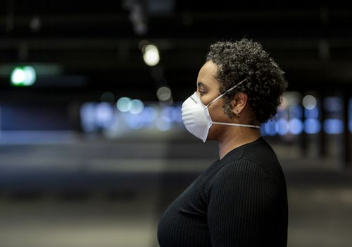 Woman standing outside in mask