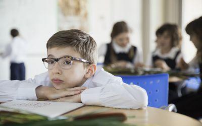 Bored school boy in classroom