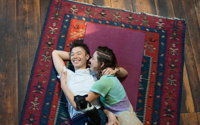 two woman hugging on a rug on the floor