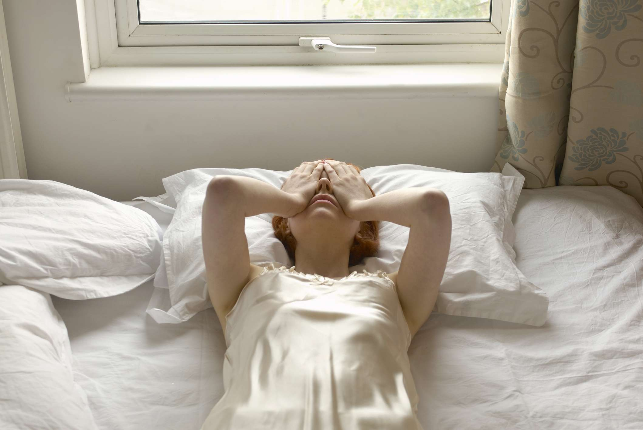 Woman stressed while laying on bed
