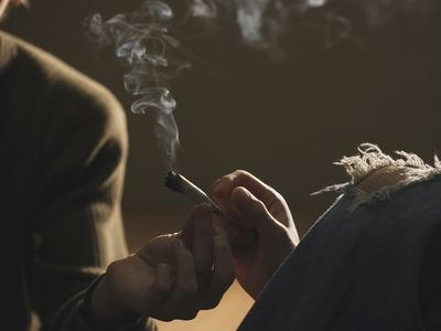 Hands passing marijuana joint