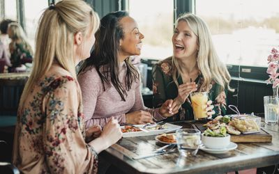 A front view shot of three beautiful mid-adult women enjoying brunch together in a restaurant, they are sitting around a table and laughing with each other.