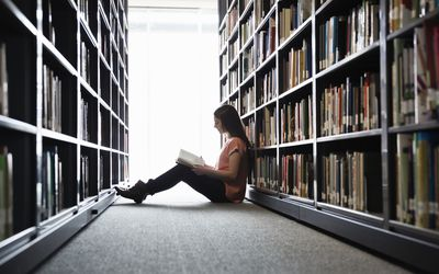 Woman sitting on the floor in the library stacks reading