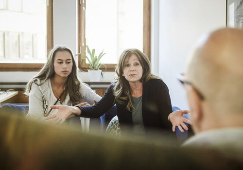 Mother sitting with daughter while sharing problems to male therapist at community center