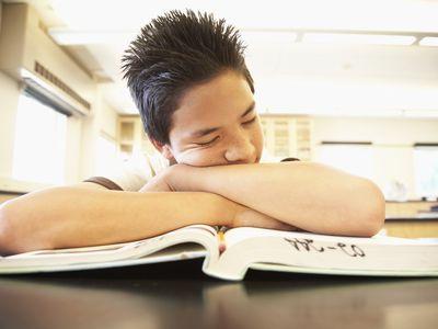 Young boy asleep on textbook