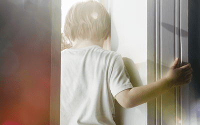sad child holding door frame