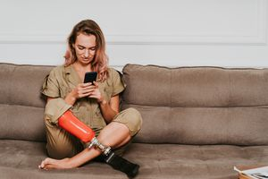 Woman with prosthetic leg sitting on a couch and using a smartphone