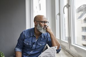 Mature man sitting at window looking worried