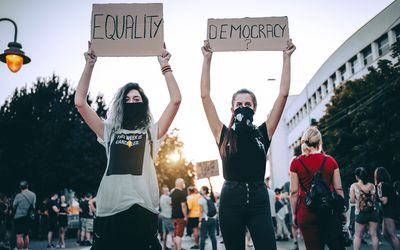 Young women protesters holding placards