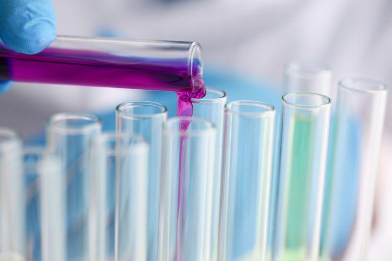 Male chemist holds test tube of glass in hi