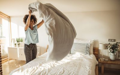 Young woman making bed at home. She is in pajamas. Doing her morning routine.