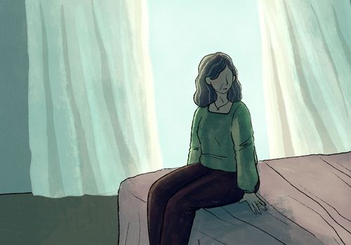 Woman sitting on bed, looking off to the side